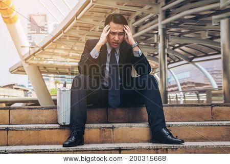 Desperate Businessman Sitting Hopelessly On Stair Floor