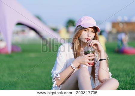 Young beautiful girl hipster drink refreshing lemonade red resting in the park. Summer concept.