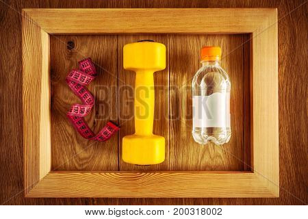 Dumbbells measuring tape and a bottle of water in a frame on a wooden background