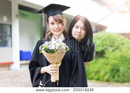 Beautiful young female graduate holding flowers and Mother hugged her at graduation ceremony.