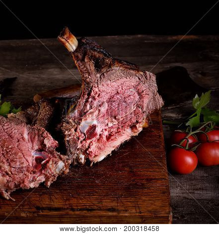 grilled beef  meat on a wooden table close up on a dark background