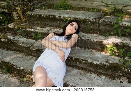 Beautiful young woman in white dress lying on the stairs of old abandoned castle, dark mystery scene