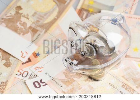 Piggy bank coins and euro bills. Money saving concept. Banknotes closeup isolated background.