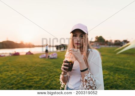 Portrait of a bridal young woman standing against the background of the sun with lemonade in his hands. Walk around the park.