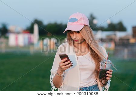 A stylish young woman with a lemonade in her hands uses a voluptuous phone in the background of the park. Summer concept. Holiday at the festival.