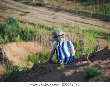 The child sits on the mountain. High altitude. At the bottom of the field.