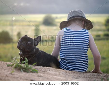 The child sits on the mountain with the dog. High altitude. At the bottom of the field.