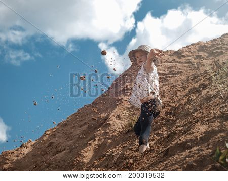 Child on the mountain of sand. Blue sky. A little girl throws sand. Journey with the concept of children