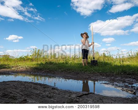 A child with a shovel in a vacant lot in the field. The concept start of construction of the future house the revival of agriculture
