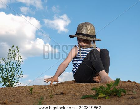The child is sitting on a mountain of sand. Blue sky. A little girl wearing a hat and barefoot. Journey with the concept of children