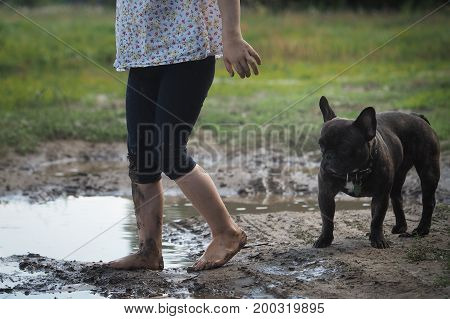 The child's foots in the mud. Dog