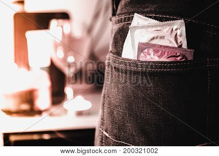 Vintage image style. Condoms in package in jeans with blurred party background. Protection against AIDS. Safe sex concept. contraception and birth control. Protection against unwanted pregnancy.