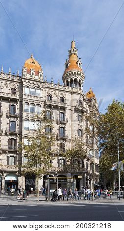 Barcelona - October 10 2015: Beautiful apartment building with a tower and with a shop and people at a bus stop of the city October 10 2015 Barcelona Spain