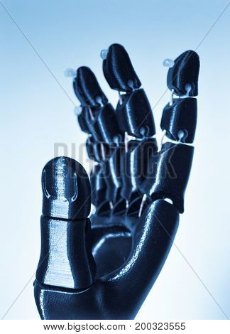 Robot hand fingers from plastic close-up. Automatic three dimensional performs plastic modeling. Modern 3D printing technology.