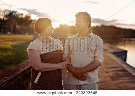 Elderly couple walking talking laughing at the sunset near the lake river