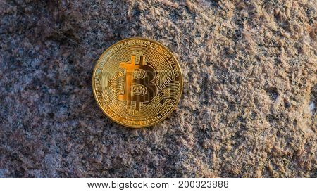 Golden Bitcoin On Stone Surface. Close-up View