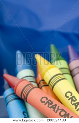 Bunch of colorful crayons on blue background