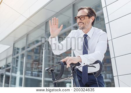 Senior businessman with a bike outside listening music