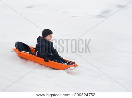 Little boy enjoying sleigh ride. Toddler kid riding a sledge. Children play outdoors. Kids sled in snowy park in winter.