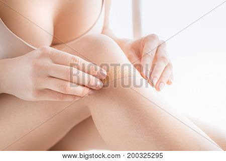 Young female body care at home stick plaster