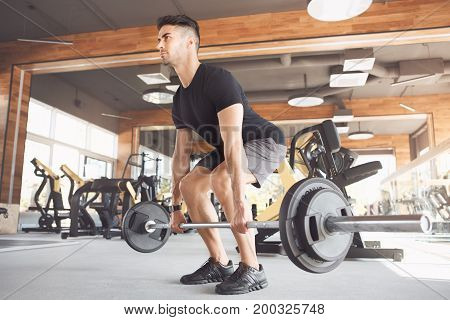 Young male exercise in the gym with barbell