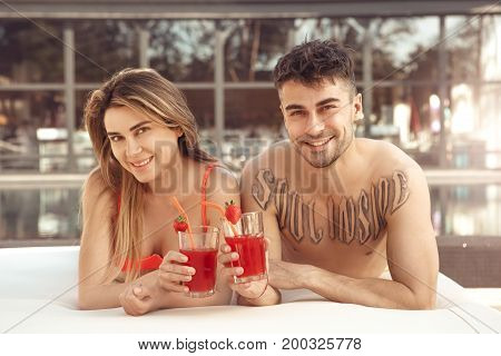 Young man and woman rest together near swimming pool drinking cocktail