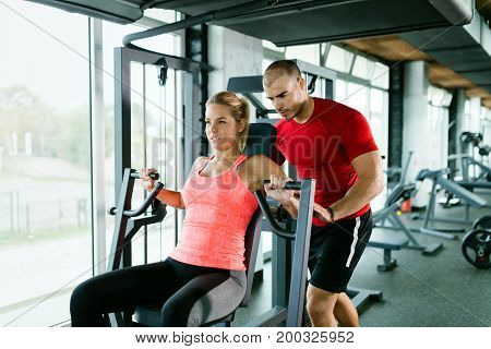 Beautiful girl working out in gym with personal trainer