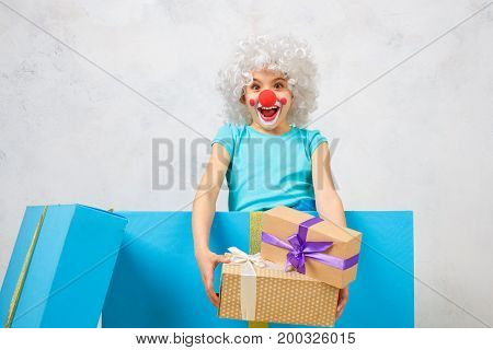 Little child wearing clown costume birthday celebration inside a gift box