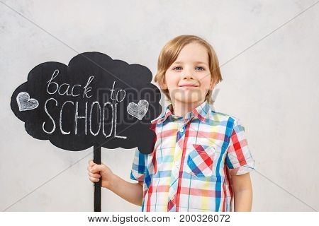 Little blonde kid isolated on white holding back to school banner