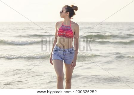 Young woman in blue denim shorts and colorful swimsuit top at the beach. Young female walking at the seashore. Vacation freedom and enjoyment