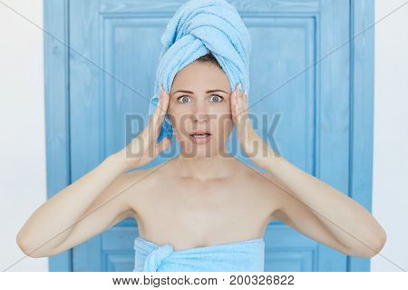 Omg! Young Caucasian blue-eyed housewife with towel on her head after shower keeping hands on her templeshaving shoked or frightened look having forgot to do something important. Human face expressions and emotions.
