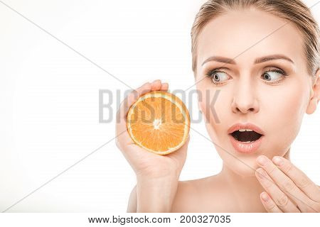 Mature female beauty health care studiio portrait holding orange