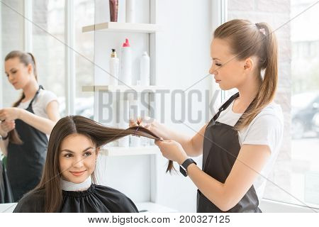 Young female sitting in hair salon hairdo styling pinch with hairpin