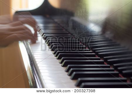 Hands playing piano with narrow field of focus