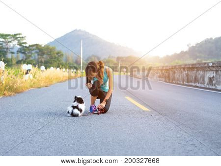 Puppy dog and young women running exercise on the street park in the morning. Young woman teaching her puppy dog obedience gesturing with her finger for it to sit or stay