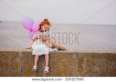 adorable little girl with teddy bear and balloons sitting on quay