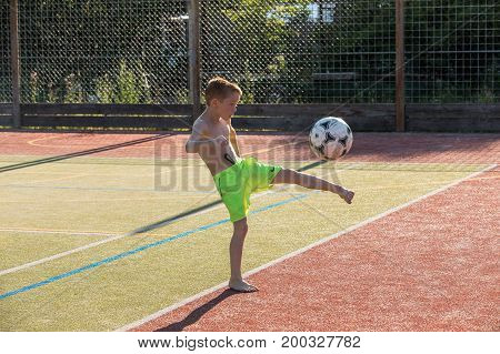 HRISTE Czech Republic June 6 2017. Boy kicking soccer ball on sports field. Concept of sport health training athlete. Outdoor playground for tennis volleyball and football. Sport. Cute boy.
