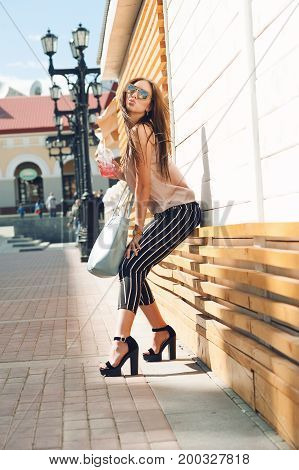 Outdoor portrait of a young beautiful fashionable happy lady wearing sunglasses, in a wooden frame, on a city street. The model wears stylish clothes, a beige blouse, black breeches in a white strip, a bag of light-blue. The girl looks at the camera and s