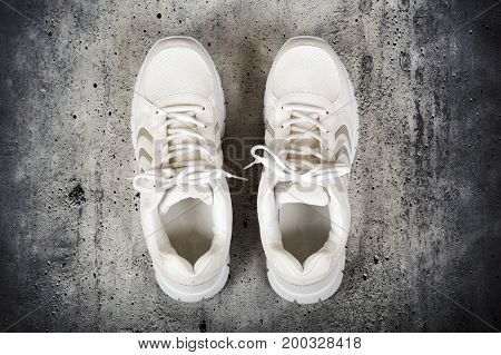 Pair of white sports shoes with laces isolated on a concrete background