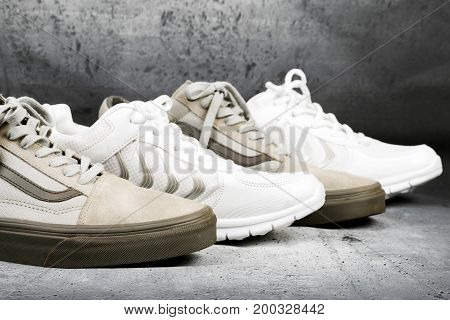 Sports shoes standing in a row on a concrete background