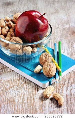 A bowl with snacks nuts and apple stationery a notebook and pencils back to school and learning concepts selective focus