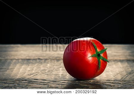 One tomato on wooden table. Close up