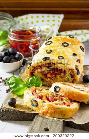 Italian Cake Pizza With Salami, Cheese, Herbs, Olives And Sun-dried Tomatoes On A Stone Or Slate Bac