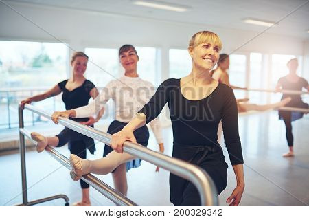 Group of adult ballerinas exercising and doing gymnastics at handrail in the ballet class.
