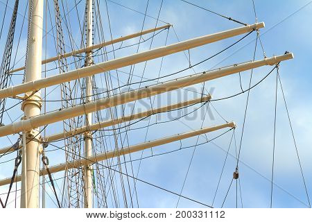 Mast of a large sailing ship against a blue sky.