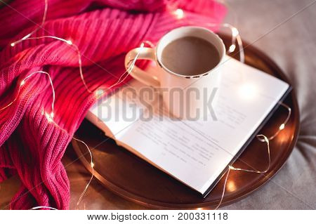 Cup of coffee stay on open book on round wooden tray with knitted sweater and christmas lights. Good morning.