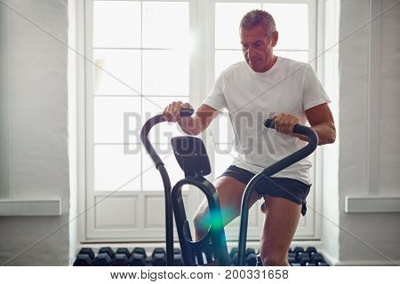 Fit Mature Man In Sportswear Cycling Alone In A Gym