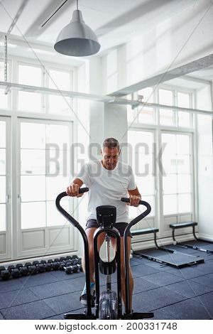 Mature Man In Sportswear Straining While Riding A Stationary Bik