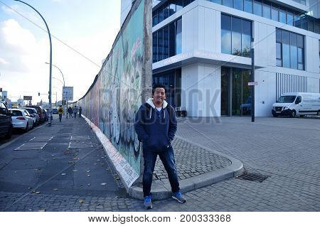 Thai Man Traveler Visit And Posing For Take Photo With The Berlin Wall (painted On The Eastern And W