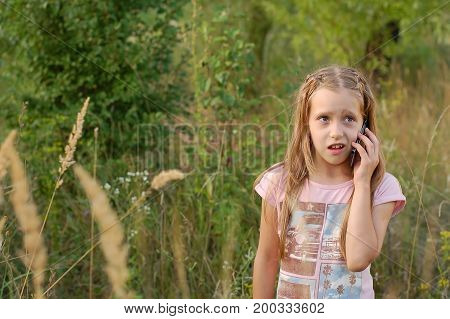 Girl talking on the phone outdoors. She has surprised face